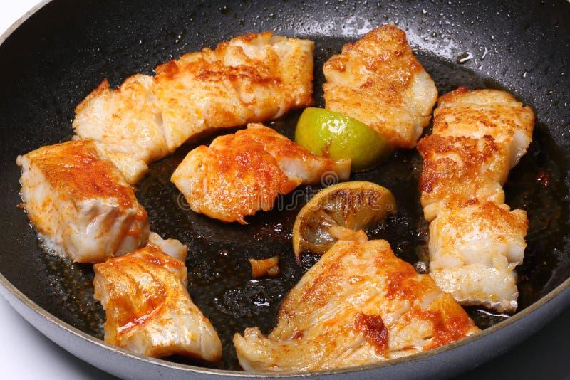 Vissen die in een pan met citroen braden stock afbeelding