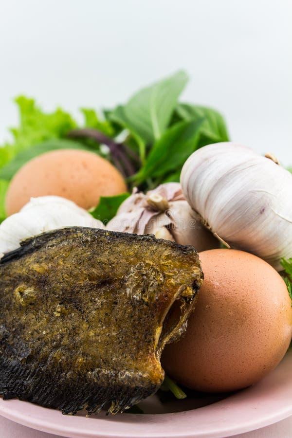 Vissen en eieren met groenten op geïsoleerde kom stock foto's