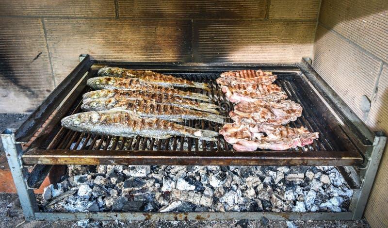Vissen en lapje vlees op de houtskoolgrill samen stock foto