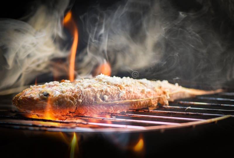 Vissen op grill/Dichte omhooggaand van zeevruchten geroosterd vissenvoedsel met zout op de de grillbrand en rook stock afbeelding