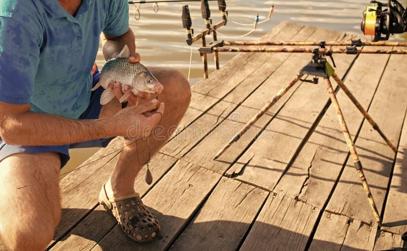 Vissen op mond in mannelijke handen worden vastgehaakt, aas visserij die royalty-vrije stock afbeeldingen