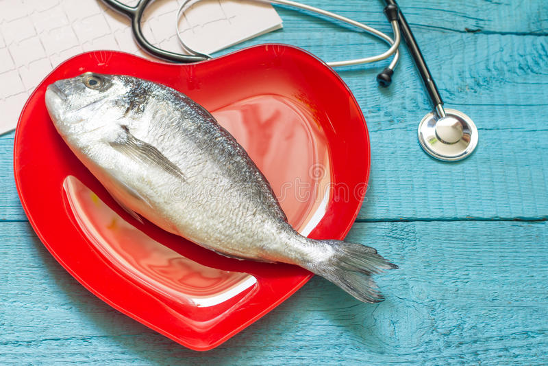 Vissen op rode hartplaat en stethoscoop stock afbeelding