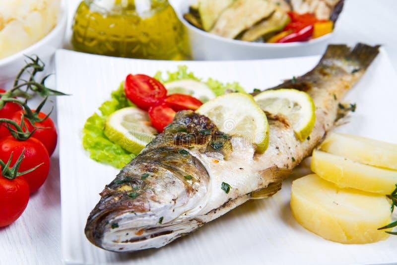 Vissen, overzeese die baarzen met citroen worden geroosterd, salade en aardappels royalty-vrije stock foto's
