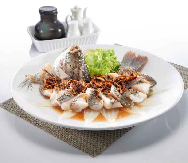 Vissen in sojasaus, die op witte plaat wordt gediend stock afbeelding