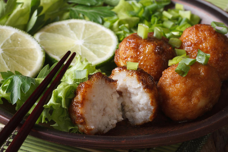 Vissenballen met kalk en salade op een plaatmacro horizontaal stock foto