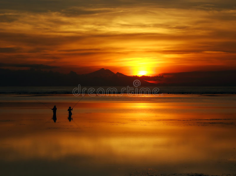 Vissend bij dageraad onder een ongelooflijke oranje zonsopgang, Bali. royalty-vrije stock foto