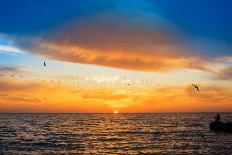 Vissend in de avond, een silhouet van een visser met een fishi royalty-vrije stock afbeeldingen