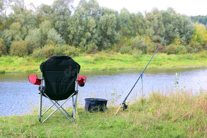 Vissend stoel, staaf en aas op de rivierbank stock afbeelding