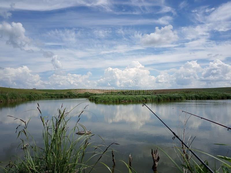 Vissende tijd? visser in het meer, dichtbij aan zonsondergang stock afbeelding
