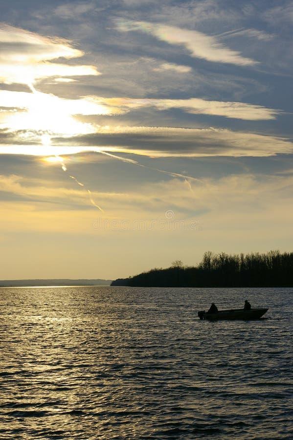 Vissende Vissers op Meer met Toneelzonsondergang stock afbeeldingen