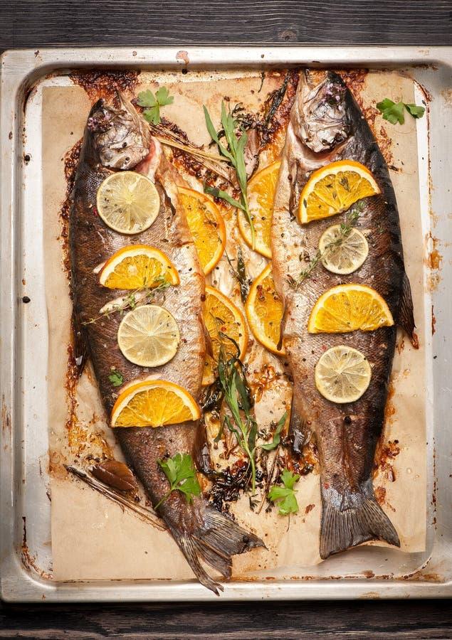 Vissenforel met sinaasappel, kalk en kruiden wordt gebakken dat stock foto's