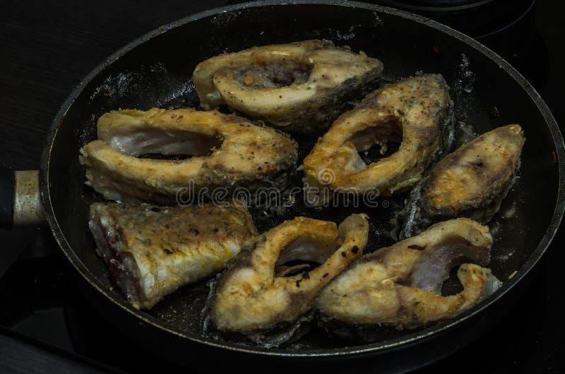 Vissenkarper in een pan wordt gebraden die stock afbeelding