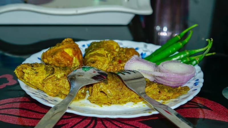 vissenkerrie, ui, Spaanse pepers op een plaat op de eettafel stock afbeelding
