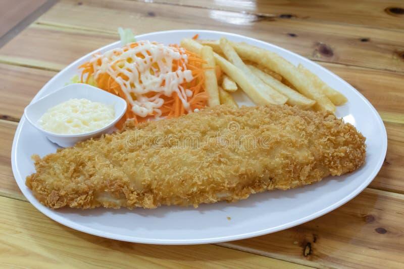 Vissenlapje vlees met frieten en salade stock afbeelding