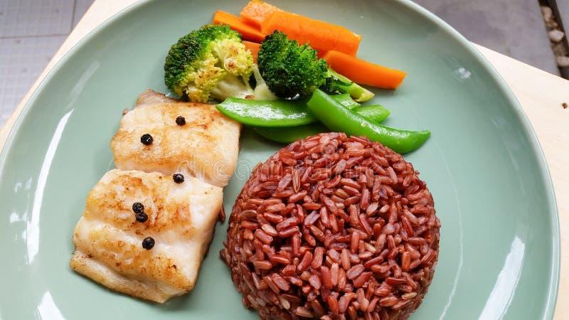 vissenlapje vlees met ongepelde rijst en groenten in groene plaat royalty-vrije stock fotografie