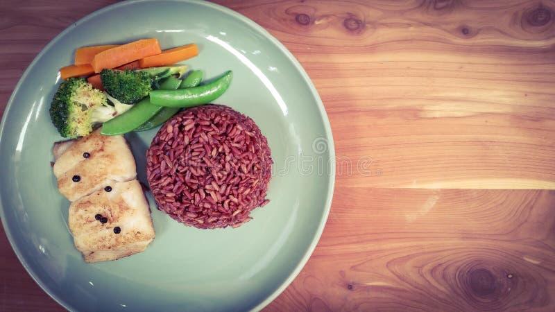 vissenlapje vlees met ongepelde rijst en groenten op houten achtergrond royalty-vrije stock foto