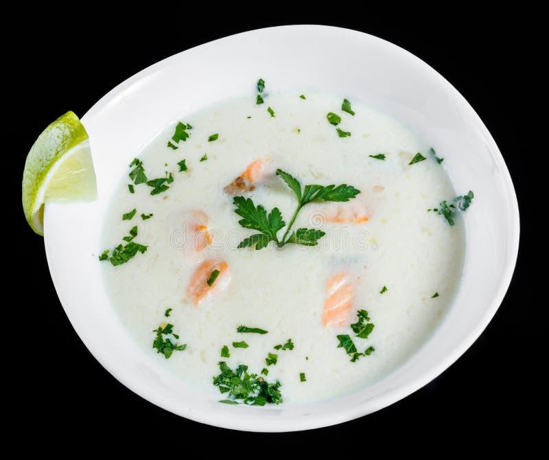 Vissensoep met zalm en garnalen, peterselie en citroen in kom, op zwarte achtergrond wordt geïsoleerd, gezond voedsel dat royalty-vrije stock foto's