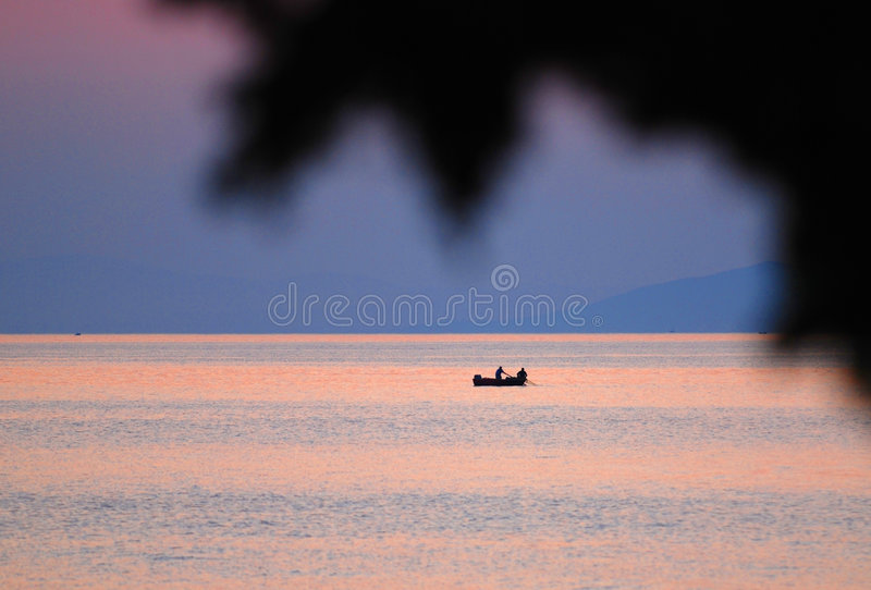 Visser in boot bij zonsondergang royalty-vrije stock fotografie