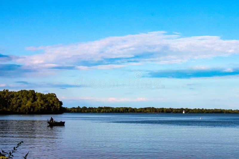 Visser in boot op meer met zeilboot in de afstand - Meer Erie royalty-vrije stock fotografie