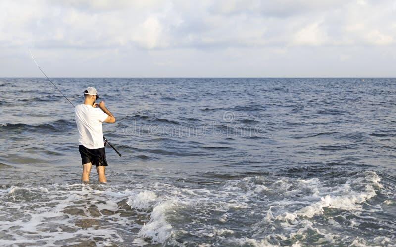 Visser de status bij de kust haakt een vis vast royalty-vrije stock foto's