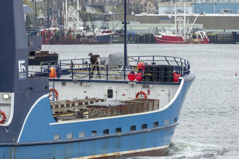 Visser die aan lijnen op boog van commerciële vissersvaartuig Overzeese Observateur II werken royalty-vrije stock fotografie