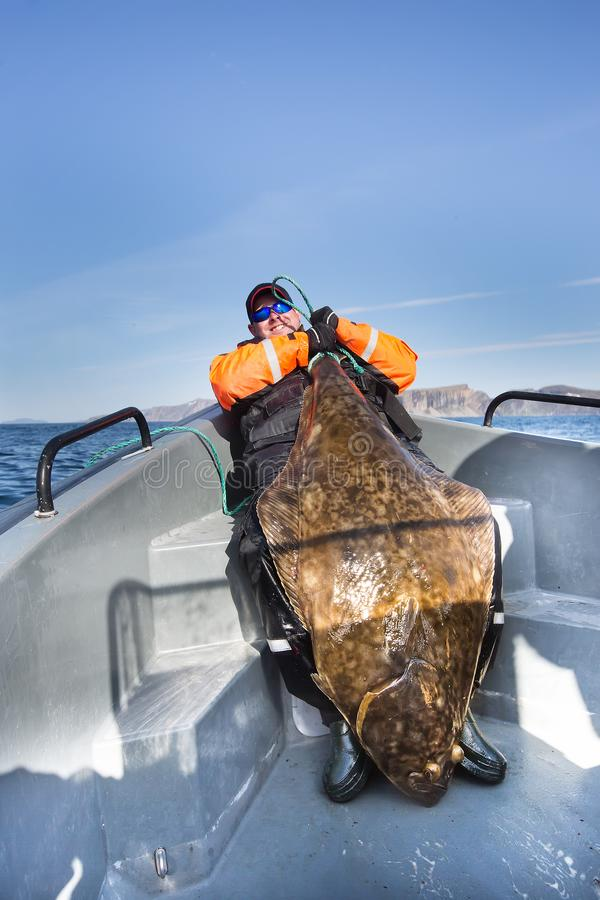 Visser die de staart van een reusachtige vis houden Verticaal schot royalty-vrije stock foto's