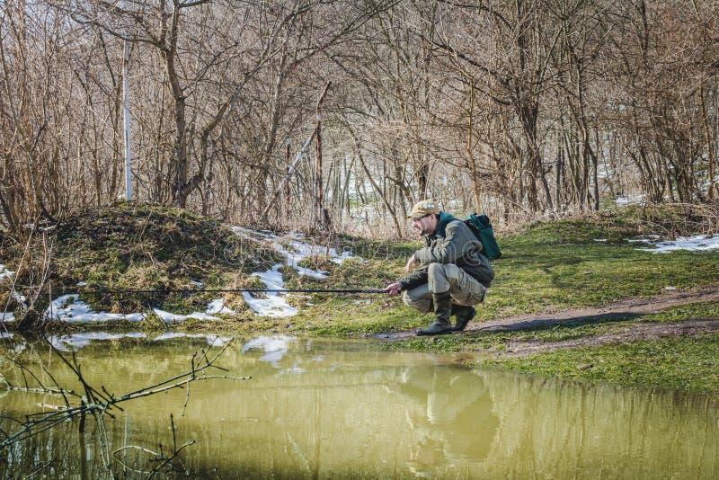 Visser die door het water in de winter vissen royalty-vrije stock afbeeldingen