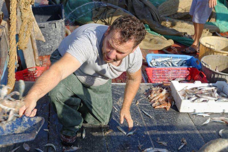 Visser die het dek van een treilerboot schoonmaken het afval harde werk royalty-vrije stock afbeelding