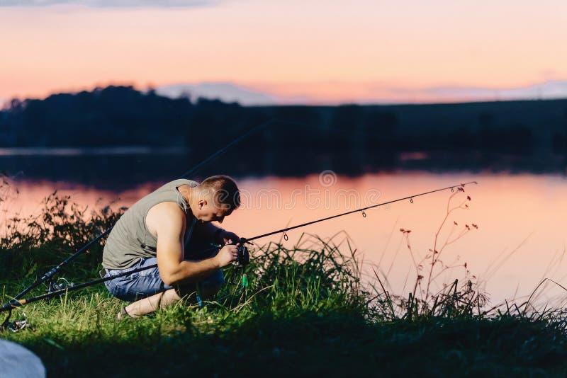 Visser die karper vangen bij meer in de zomertijd bij avond stock afbeelding