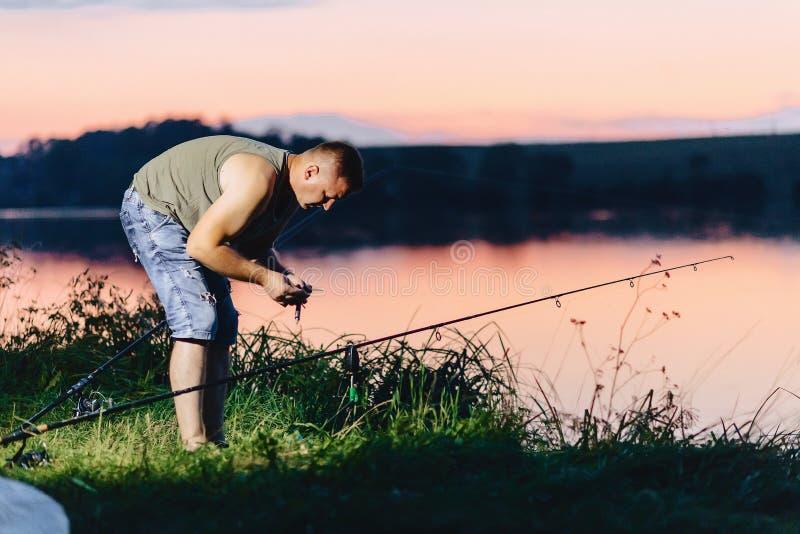 Visser die karper vangen bij meer in de zomertijd bij avond stock foto's