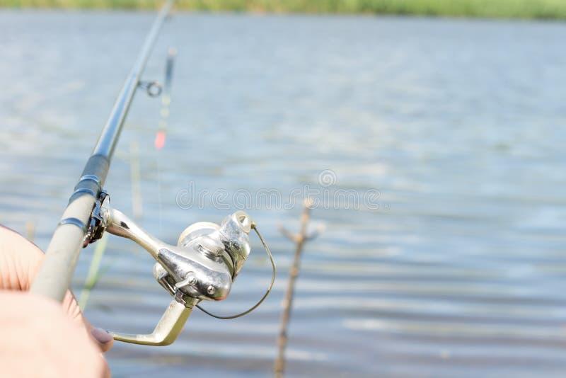 Visser die met een staaf en een spinnende spoel vissen stock foto