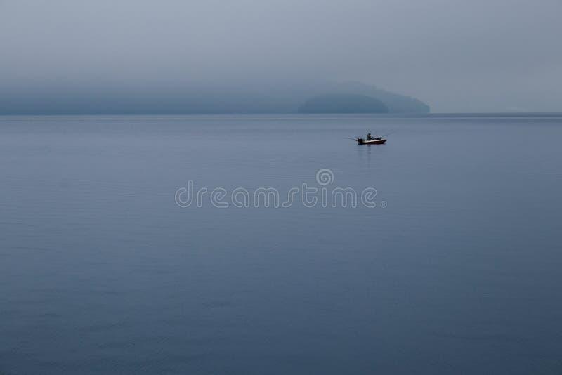 Visser die in snelheidsboot vissen, de boot die die in Toya Lake drijven met mist in bewolkte dag in Japan wordt omringd royalty-vrije stock afbeelding