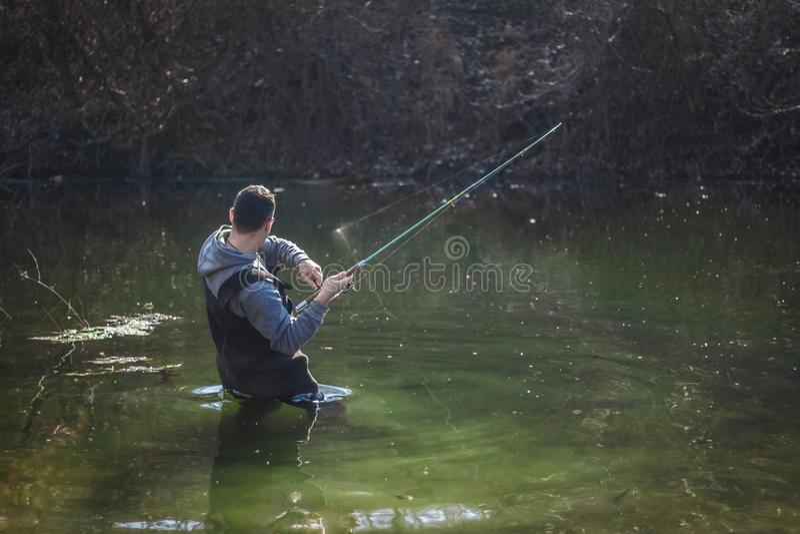 Visser die zich in water en het vechten vissen bevinden stock afbeelding