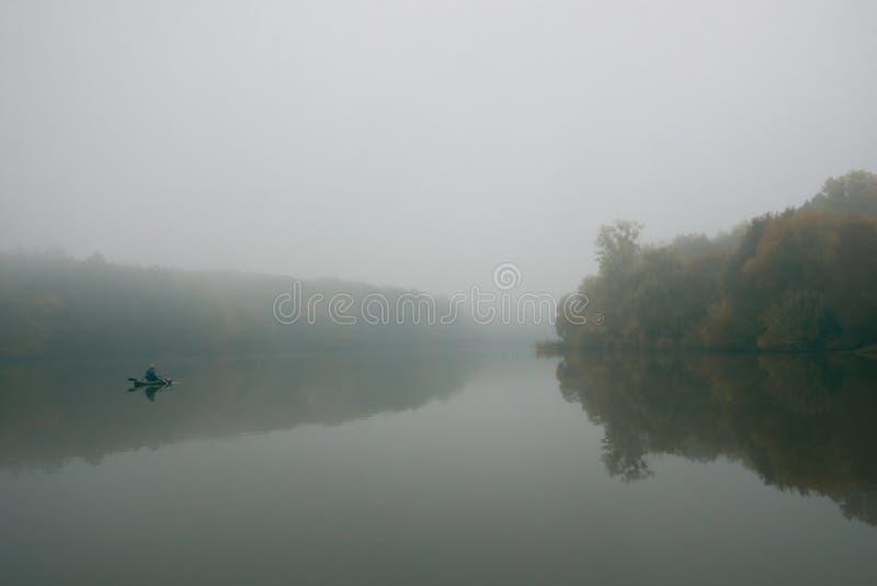 Visser in een rubberboot die met staven op een klein meer, diepe mist op een koude de herfstochtend vissen royalty-vrije stock foto's