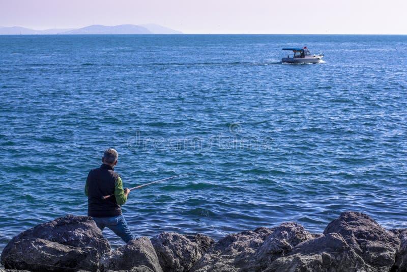Visser en boot in het overzees Dijk in Istanboel royalty-vrije stock fotografie