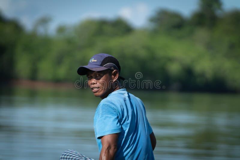 Visser in kleine boot en blauw overhemd royalty-vrije stock foto