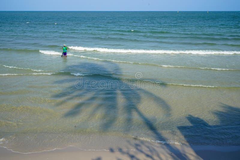 Visser in kleurrijk overhemd en broek die op visserij op het strand met zachte overzeese golf, kokospalmschaduw en blauwe hemel w royalty-vrije stock foto