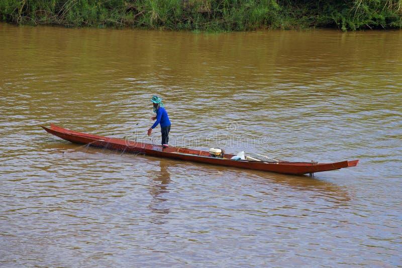Visser met een net op een houten boot op de Ruak-Rivier stock afbeelding