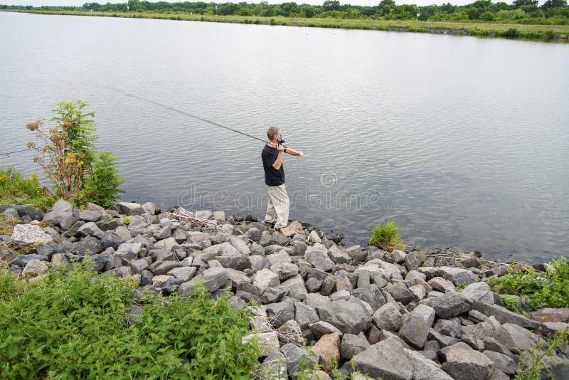 Visser met hengel op de rivierbank stock afbeeldingen