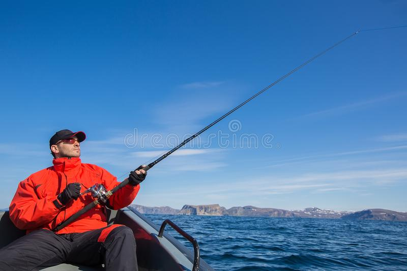 Visser met spinnende atleet in zijn handen Visserij van een boa stock foto