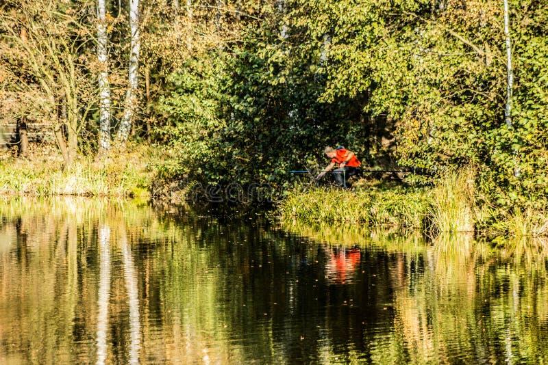 Visser op de rivierbank De herfst mooi landschap stock afbeelding