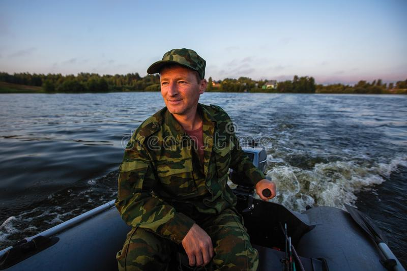 Visser op de rubbervlotters van de motorboot op het meer hobby royalty-vrije stock fotografie