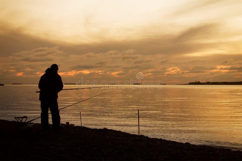 Visser op een overzeese kust en majestueuze zonsondergang over water royalty-vrije stock afbeelding