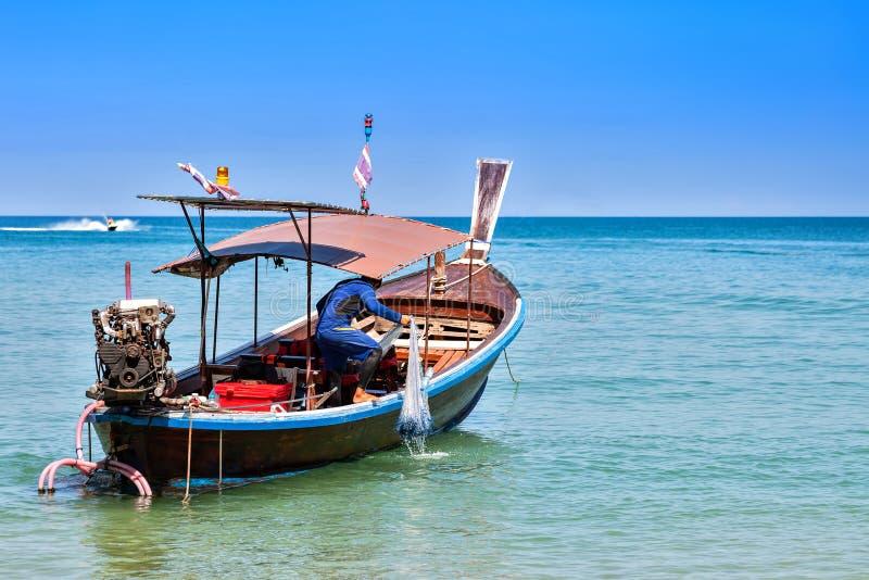 Visser op een trekkrachtvisnetten van de motor houten boot Zonnige dag, blauwe hemel en overzees stock foto