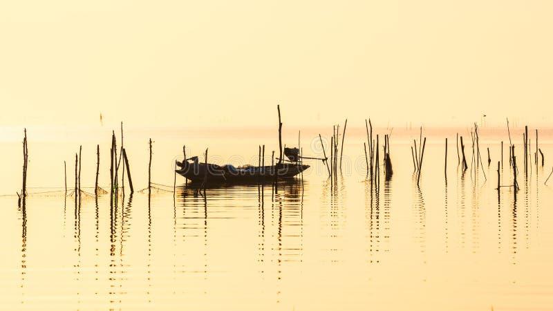 Visser op lange staartboot in meer op zonsopgang bij Pakpra-dorp stock fotografie