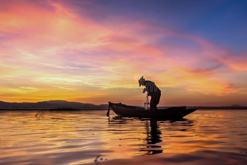 Visser op vissersboot bij oever van het meer met vissersboot stock afbeelding
