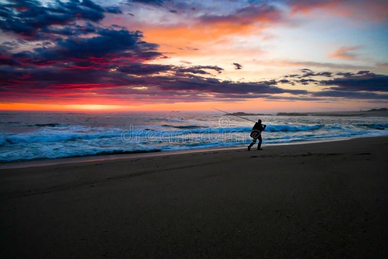 Visser in silhouet bij zonsondergang op strand royalty-vrije stock afbeeldingen