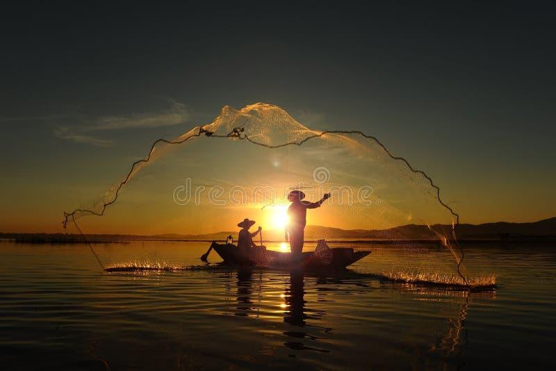 Visser van Aziatische mensen bij Meer in actie wanneer visserij tijdens zonsopgang stock afbeelding