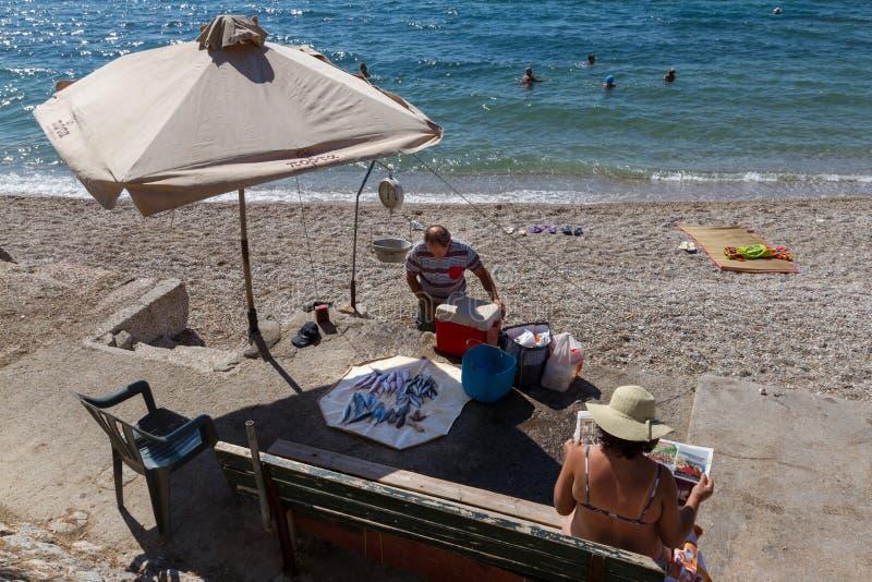 Visser, vangst en de krant van de vrouwenlezing op een strand royalty-vrije stock afbeelding