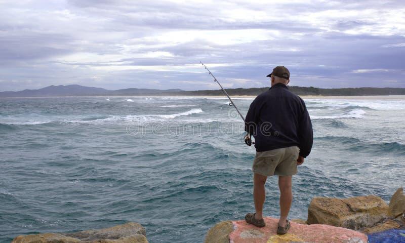 Visser visserij die zich op rots in Australië bevindt stock fotografie